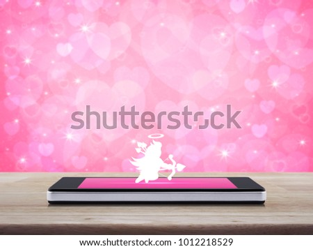 Cupid Icon On Modern Smartphone Screen Wooden Table Over Blur Pink Heart Background Internet