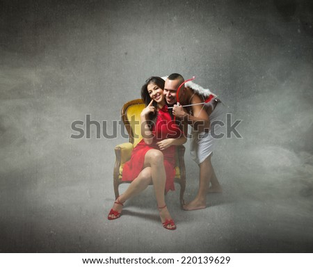 Cupid kiss a pretty girl in red dress - stock photo