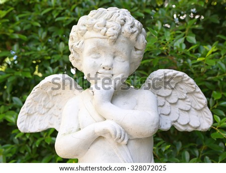 Cupid sculpture in the garden - stock photo