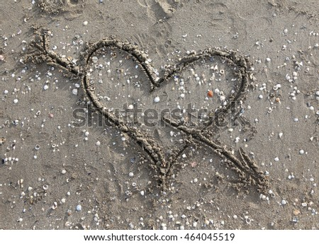 cupid symbol with heart drawn on the Beach