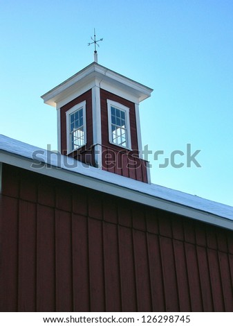 Cupola with a weathervane on the roof of an old barn on a snowy morning. - stock photo