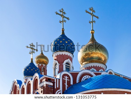 Cupolas of Russian orthodox church against blue sky - stock photo