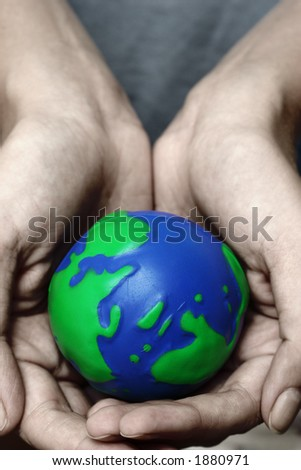 Cupped hands holding planet Earth - stock photo
