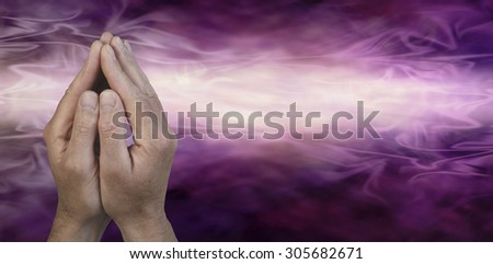 Cupped Hands in Prayer Position -  Male hands cupped together in prayer position on a dark purple and light pink energy streaming graduated background with plenty of copy space on the right hand side  - stock photo