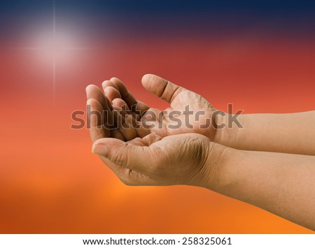 Cupped open empty hands blurred sunset light background. - stock photo