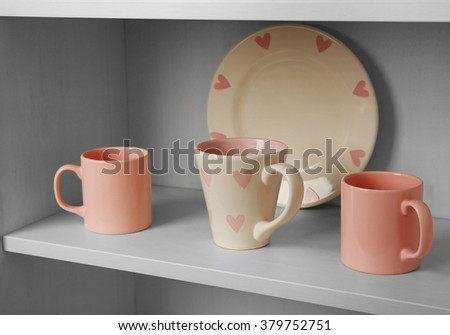 Cups and plate in cupboard in the kitchen - stock photo