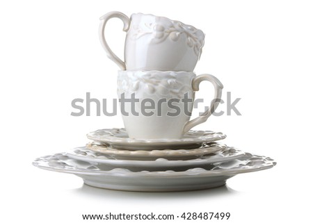cups and plates and saucers on a white isolated background - stock photo
