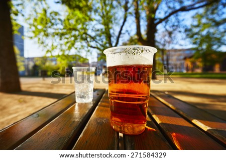 Cups of beer and water in the garden restaurant - stock photo