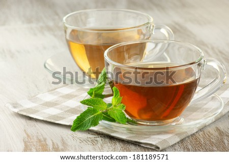 Cups of black and green tea with mint on rustic table. - stock photo