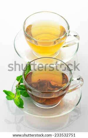 Cups of black and green tea with mint on white background.