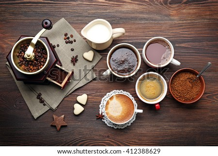Cups of coffee with beans on wooden table, top view - stock photo