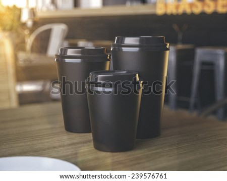 Cups of different sizes on cafe table - stock photo