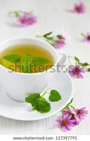 cups of green tea with mint on wooden table