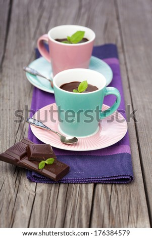 Cups of hot chocolate with mint on old wooden table - stock photo