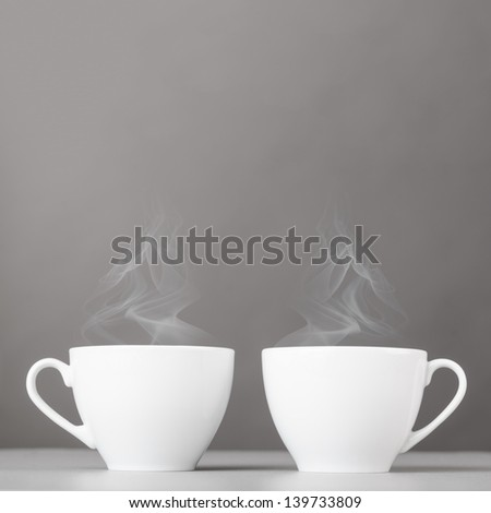 cups of hot coffee on gray background - stock photo
