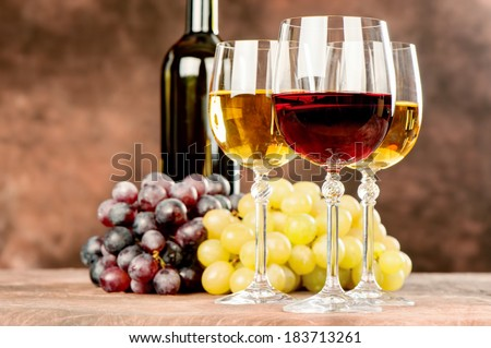 cups of red and white wine in front of grape and bottle - stock photo
