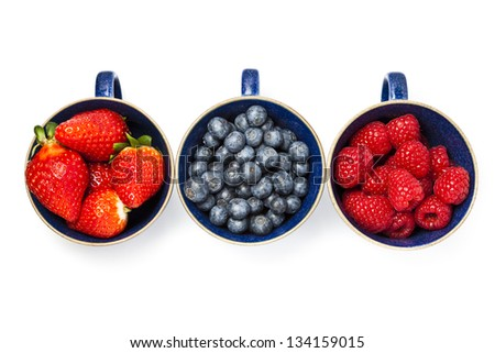 Cups of strawberries, blueberries and raspberries in a line