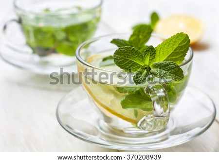 cups of tea with fresh mint and lemon slices on a blue wooden background - stock photo