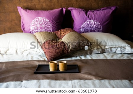 cups on a bed in a hotel room. - stock photo