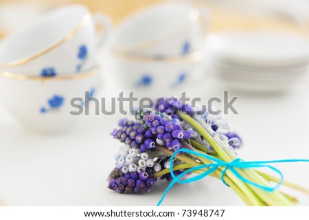 cups on a tray with a bouquet of muscari - stock photo