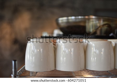 Cups on the shelf with blue coffee beans in the back