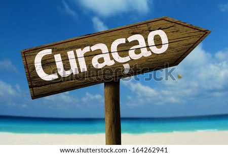Curacao, Caribbean wooden sign with a beach on background  - stock photo