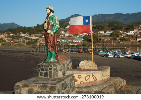 CURANIPE, CHILE - APRIL 20, 2015: Colourfully painted statue of Saint Peter and the flag of Chile on a promontory sheltering the beach used by the fishing fleet in the village of Curanipe in Chile.  - stock photo
