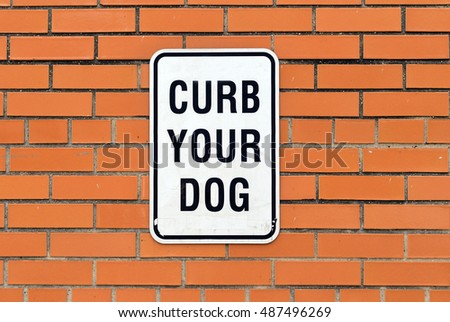 curb your dog sign on brick wall