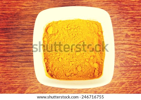 Curcuma, curry, yellow- orange spice in a bowl. Over wooden table. - stock photo