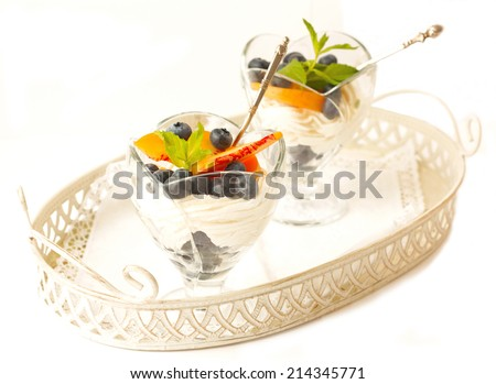 curd dessert with fresh peaches and fresh blueberries on white background horizontal - stock photo