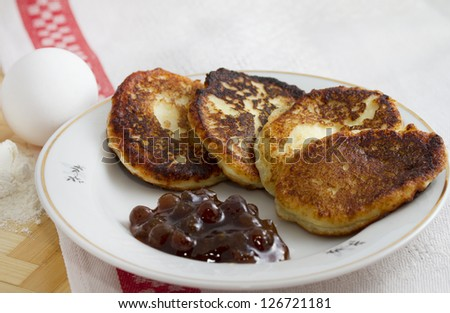 Curd pancake on a plate with strawberry jam and a handful of flour and egg