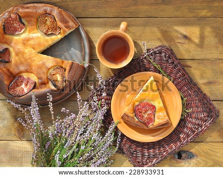 Curd pudding with figs and honey on wicker brown napkin and herbal tea with heather on the wooden background. Sheaf of heather. - stock photo