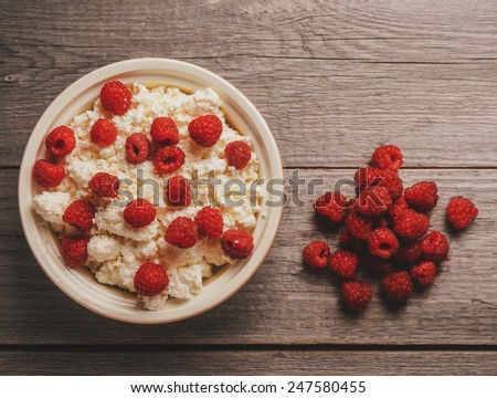Curd with ripe fresh raspberries in a bowl on wooden background, top view - stock photo
