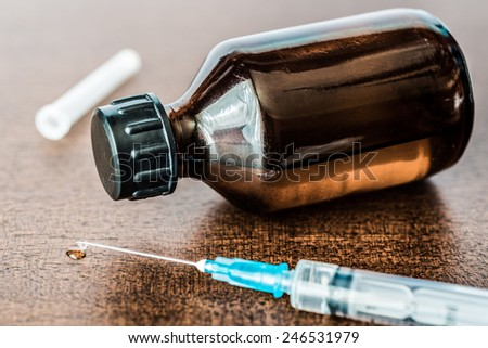Cure the disease, a solution and a syringe for injection, drug flow from the syringe. Angle view, in old tones - stock photo