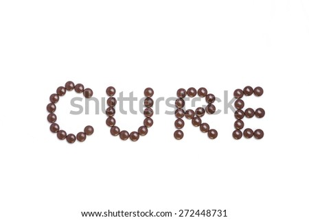 Cure written with brown pills - white background - stock photo