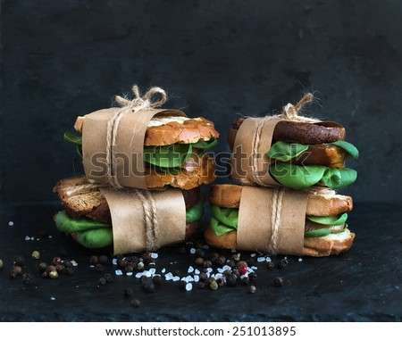 Cured chicken and spinach whole grain sandwiches placed one on another wrapped in craft paper and tied with a decoration rope  with spices and black stone background - stock photo