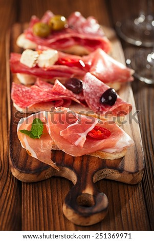 Cured Meat and ciabatta bread on wooden board, white wine on background - stock photo
