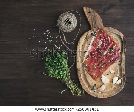 Cured pork meat or prosciutto on a rustic wooden board with garlic, spices and thyme over a dark wood background with a copy space. Top view - stock photo