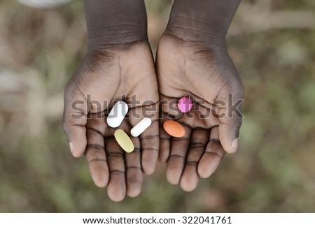 Curing Malaria - African Girl Holding Pills Medicine Health Symbol. Medicine and healthcare pills are very important in the black continent.  - stock photo