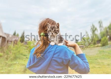 Curiosity kitten sitting on shoulder of unrecognizable little girl outdoors in summer - stock photo