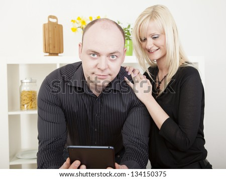Curious attractive young blonde woman reading her husbands tablet over his shoulder as he looks up at the camera with a resigned smile of forbearance - stock photo
