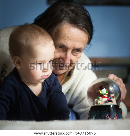 Curious baby and his grandmother are looking at the snow paper weight on the bed.  Interaction between young boy and old woman. Shot of grandmother with her grandson. - stock photo