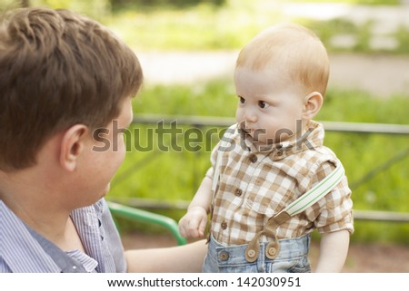 Curious baby boy son looks questioningly at father during the play - stock photo
