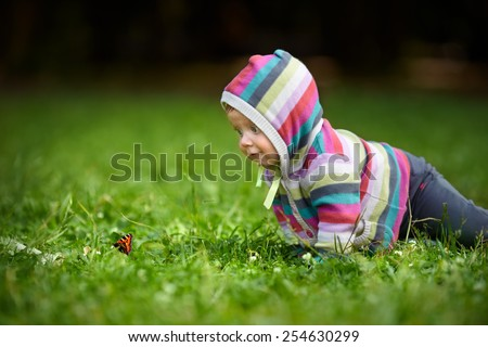 Curious baby in striped dress crawling on a green lawn to the butterfly. The child first saw a butterfly and looks very surprised
