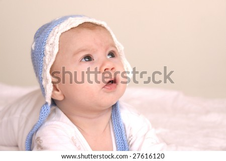 Curious baby wearing blue hat