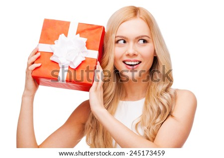 Curious beauty. Curious young blond hair woman holding gift box and trying to guess what is inside while standing isolated on white background - stock photo