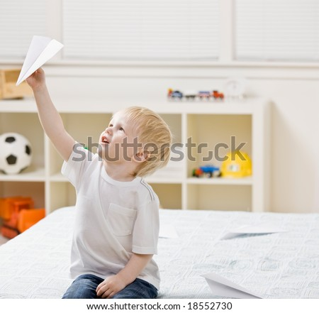 Curious boy flying paper airplane in bedroom