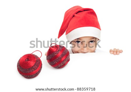 curious boy in red hat with two christmas decorative balls isolated on white background with empty copy space to place advert or banner - stock photo