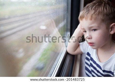 Curious boy looking out the window of a speeding train