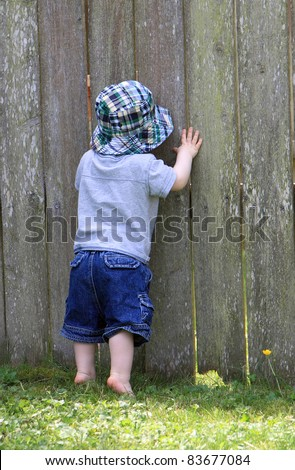 Curious boy peeks through hole in fence to see what is on other side - stock photo
